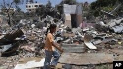 دختری فلسطینی که روی مخروبه های منازل قدم میزند.