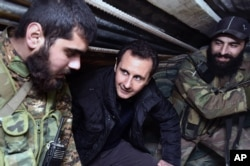 FILE - Syrian President Bashar Assad, center, speaks with Syrian troops during his visit to the front line in the eastern Damascus district of Jobar.