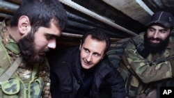 FILE - Syrian President Bashar al-Assad, center, speaks with Syrian troops during his visit to the front line in the eastern Damascus district of Jobar, Dec. 31, 2014.