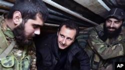 Presiden Suriah Bashar Assad, tengah, berbicara dengan pasukan Suriah ketika berkunjung ke distrik Jobar, Damaskus. (Foto: dok.)
