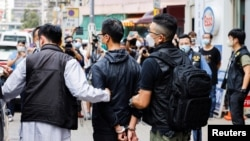 Leung Kam-wai, one of the arrested members of the Hong Kong Alliance in Support of Patriotic Democratic Movements of China, is escorted by police as they leave after a search of the June 4th Museum, in Hong Kong, Sept. 9, 2021.