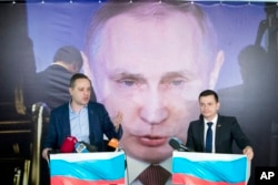 "Russian opposition activists Ilya Yashin, right, and Vladimir Milov present their report ""Putin. Results. 2018"" in front of a poster displaying Russian President Vladimir Putin in Moscow, Russia, Wednesday, March 14, 2018"