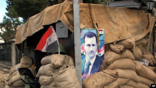 Hunkering down: a poster of Syria's president at a checkpoint on the outskirts of Damascus, January 2012.