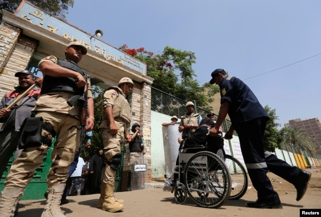 Soldiers stand guard outside a polling station on the second day of voting in the Egyptian election in Cairo, May 27, 2014.