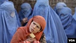 """Seorang gadis Afghanistan bersama para perempuan Afghan lainnya menunggu distribusi makanan di tempat penampungan """"KinderBerg International"""" bantuan pemerintah Jerman di Kunduz (foto: dok.)."""