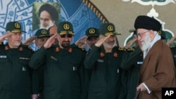 FILE - Ayatollah Ali Khamenei arriving at a graduation ceremony of the Revolutionary Guard's officers, as the deputy commander of the Guard, Hossein Salami (2nd R) and other salute him in Tehran. (Office of Iranian Supreme Leader via AP)
