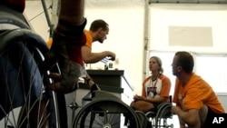Para teknisi berbicara dengan seorang atlet di bengkel pembuatan kursi roda (foto: dok).