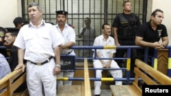 Police guard Egyptian activist Ahmed Douma (C), who is seen behind bars, during his trial at the New Cairo court, on the outskirts of Cairo, Egypt, June 3, 2013.