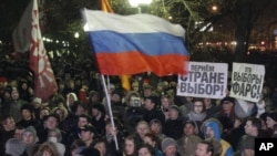 "People wave the Russian flag and hold posters reading ""This election is farce!"" and ""Give the country choice back"" during an opposition rally in Moscow, Russia, December 5, 2011."