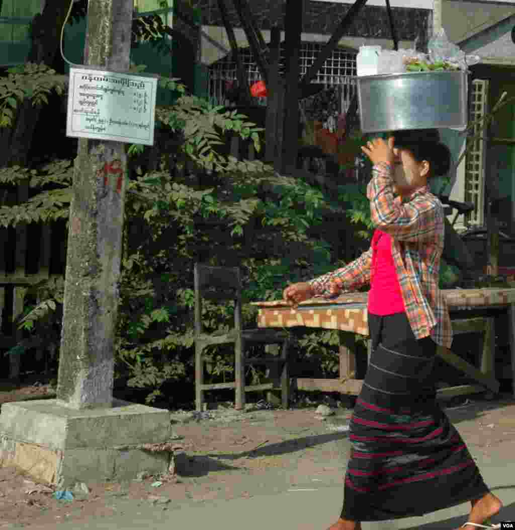 A longyi-clad woman with thanaka on her cheeks carrying food. (Steve Herman/VOA News)