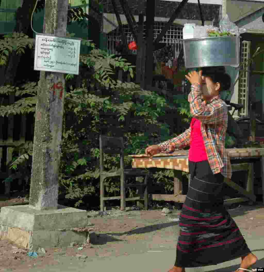 Seorang perempuan mengenakan sarung longyi dan bedak dingin thanaka di pipinya sambil membawa makanan. (VOA/Steve Herman)