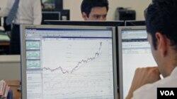 Seorang pialang saham di Paris mengamati pergerakan indeks di komputernya. Saham Eropa kembali anjlok akibat kekawatiran soal utang.