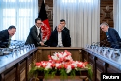 FILE - U.S. Secretary of State Mike Pompeo, left, Afghan President Ashraf Ghani, center, and Afghan Chief Executive Abdullah Abdullah, right, arrive for a meeting at the Gul Khanna in the Presidential Palace in Kabul, Afghanistan, July 9, 2018.