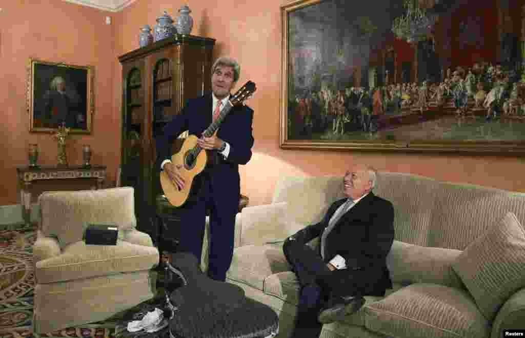 U.S. Secretary of State John Kerry (L) poses with a guitar, given as a present by Spanish Foreign Minister Jose Manuel Garcia-Margallo, during a meeting at the Foreign Ministry in Madrid, Oct. 18, 2015.