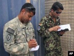 Sergeant First Class David Lara, left, is putting Afghan Air Force flight medics through their paces as he works with Afghan Air Force Sergeant Hayatullah Bahar, Aug 2010