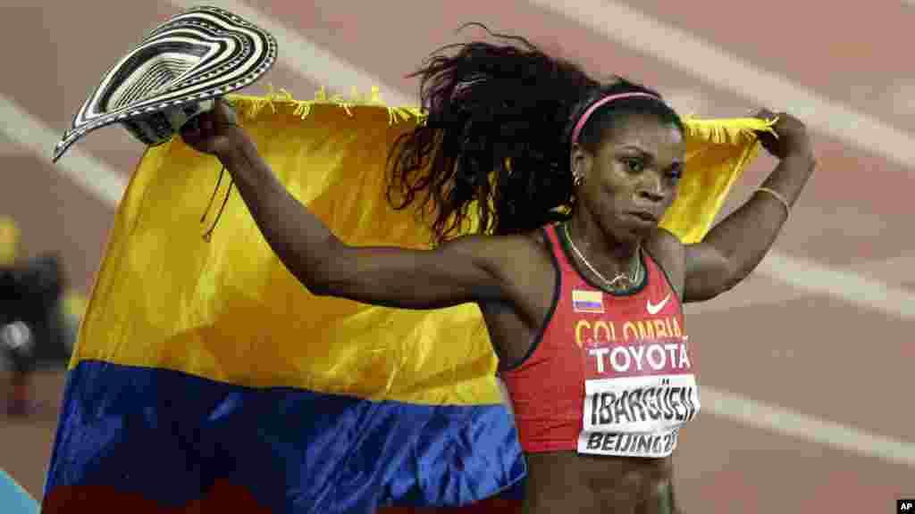 Caterine Ibarguen de la Colombie brandit le de son pays alors qu'elle célèbre après la médaille d'or qu'elle vient de remporter en finale de triple saut féminin aux championnats du monde d'athlétisme au stade Nid d'oiseau à Pékin, 24 août 2015.