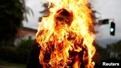 """Un monigote que representa a Nicolás Maduro es quemado durante la tradicional """"Quema del Judas"""", parte de las celebraciones de la Semana Santa en Venezuela."""