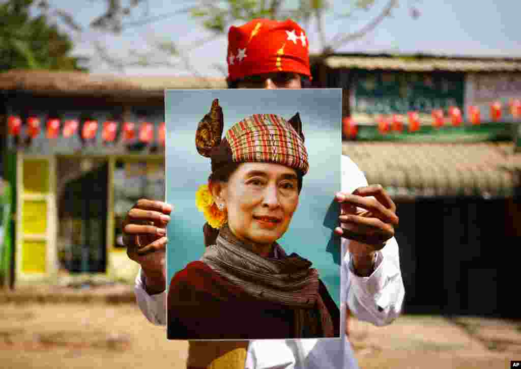 A supporter holds up a portrait of Aung San Suu Kyi during an election campaign of the National League for Democracy party in Rangoon. Burma's parliamentary election is scheduled for Sunday. (Reuters)