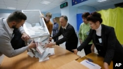 Members of a local election commission open a ballot box to count votes after a day of election at a polling station in Kiev, Ukraine, Oct. 25, 2015.