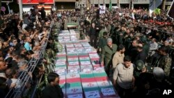 Flag-draped caskets of those who died in Saturday's terror attack on a military parade are laid out during a mass funeral, in the southwestern city of Ahvaz, Iran, Sept. 24, 2018.