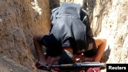 A Free Syrian Army fighter prays near a weapon in a trench in Al-Maliha, a suburb of Damascus, September 8, 2013.