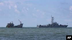 FILE - A Myanmar navy vessel tows a boat with migrants, off the country's Thameehla island, May 31, 2015.