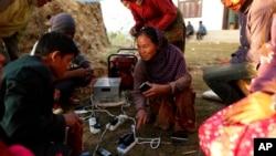 Warga Nepal korban gempa di desa Paslang mengisi baterei ponsel mereka dari sebuah generator (foto: dok). Pasca gempa, Nepal masih mengalami kelangkaan makanan.