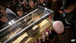 People stand around the mortal remains of Saint Pio (Padre Pio) as they are displayed in Rome's San Lorenzo Basilica, as part of the Roman Catholic Church 2016 Holy Year celebrations, Feb. 3, 2016.(AP Photo/Andrew Medichini)