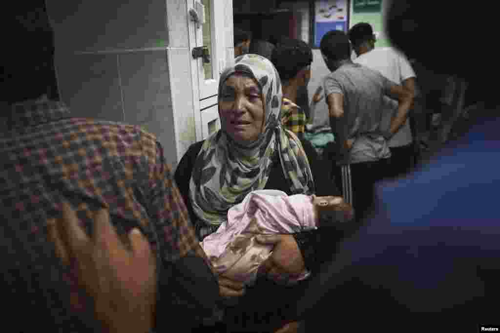 A Palestinian woman holds an infant, whom medics said was injured in an Israeli shelling at a U.N-run school sheltering Palestinian refugees, at a hospital in the northern Gaza Strip July 24, 2014.