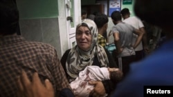 A Palestinian woman holds an infant injured at a U.N-run school.