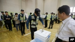 A South Korean police officer casts his early vote for the upcoming May 9 presidential election at a local polling station in Seoul, South Korea, May 4, 2017.