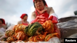 A woman makes traditional Korean side dish kimchi, or fermented cabbage, during the 2014 Seoul Kimchi Making and Sharing Festival at Seoul City Hall Plaza in Seoul, South Korea, Nov. 14, 2014.