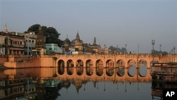 People stand on a bridge in Ayodhya, India. Schools, shops and businesses reopened in Ayodhya and other places following a court order to divide a disputed holy site between the Hindu and Muslim communities, 02 Oct 2010