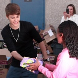 "A Warner Brothers photo of Justin Bieber handing out toys to students at Whitney Elementary School in Las Vegas, Nevada, on December 16. Bieber and ""The Ellen DeGeneres Show"" presented the students with $100,000 in toys for the holidays."