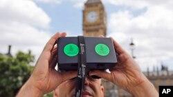 Ảnh tư liệu - Một người đàn ông nhìn qua thiết bị thực tế ảo cho thấy hình ảnh 360 độ của thành phố Aleppo, Syria, trong cuộc biểu tình của tổ chức Ân xá Quốc tế ở Quảng trường Parliament, London, ngày 11 tháng 7 năm 2015.