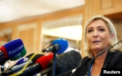 FILE - Leader of France's National Rally Party Marine Le Pen speaks during a news conference in Milan, Italy, May 18, 2019.