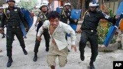 11月12日,在金邊一所佛寺大院,一名受傷的柬埔寨工人逃離防暴警察追打。