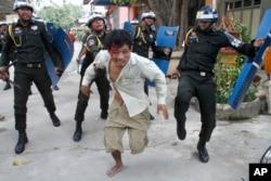 在金边一所佛寺大院,一名受伤的柬埔寨工人逃离防暴警察追打。(2013年11月12日)