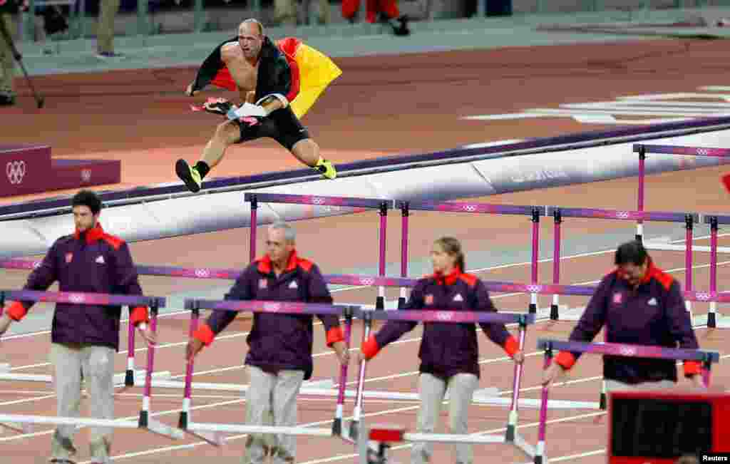 Germany's Robert Harting jumps over a hurdle as he celebrates winning the men's discus throw final. Harting won gold ahead of Iran's Ehsan Hadadi who took silver and Estonia's Gerd Kanter who won bronze.
