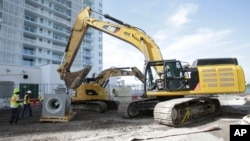 FILE - An excavator prepares to lift a storm water drainage pump on a construction site in Miami Beach, Florida.
