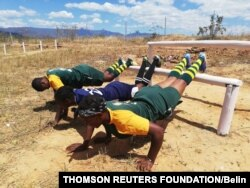 Rugby players Cathrine Muranganwa, Velme Nyarumwe and Trish Kandemiri doing press ups in a newly erected jungle gym at Sahumani Secondary. Honde Valley, September 11 2020, Thomson Reuters Foundation/Farai Shawn Matiashe