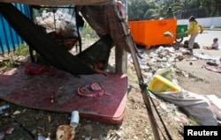 A young girl sleeps in a hammock as her mother clears garbage, along a street in central Phnom Penh October 3, 2014. REUTERS/Samrang Pring