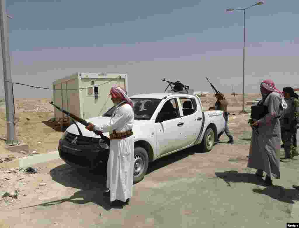 Tribal fighters carry their weapons during an intensive security deployment to fight militants of the Islamic State, in the town of Haditha, northwest of Baghdad, Aug. 25, 2014.