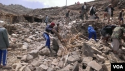 FILE - Villagers scour rubble for belongings scattered during the bombing of Hajar Aukaish, Yemen, in April 2015. (A. Mojalli/VOA)