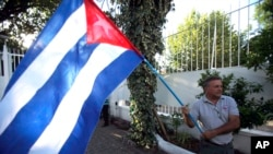 FILE - A man waves a Cuban flag while celebrating the restoration of diplomatic relations between Havana and Washington, in the courtyard of the Cuban Embassy in Santiago, Chile, Dec. 17, 2014.
