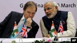 British Minister of State for Foreign and Commonwealth Office Hugo Swire, left, interacts with India's Gujarat state chief minister Narendra Modi at Gandhinagar in Gujarat, India, Wednesday, March 20, 2013. Swire was accompanied by a large business delegation including a team from UK's oil and gas major BG Group. According to local news reports, the BG Group, Wednesday signed an agreement for the supply up to 2.5 million tonnes per annum of liquefied natural gas (LNG) to the state-owned Gujarat State Petroleum Corporation Ltd. (AP Photo/Ajit Solanki)