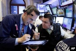 Traders Gregory Rowe, left, and Robert Finnerty work on the floor of the New York Stock Exchange, Nov. 9, 2016. Stocks are moving solidly higher in midday trading on Wall Street following Donald Trump's victory speech.