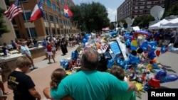 Orang-orang berpelukan di tempat peringatan penembakan polisi di markas besar polisi di Dallas, Texas, 10 Juli 2016.
