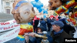 A woman inflates a balloon depicting the puppet Pinocchio with the face of Italian Prime Minister Matteo Renzi during a labor demonstration against the government in downtown Rome, Dec. 12, 2104.