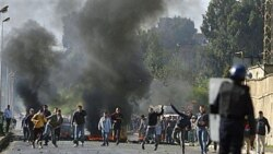 Youths clash with police officers in Algiers earlier this month after price increases on basic food staples